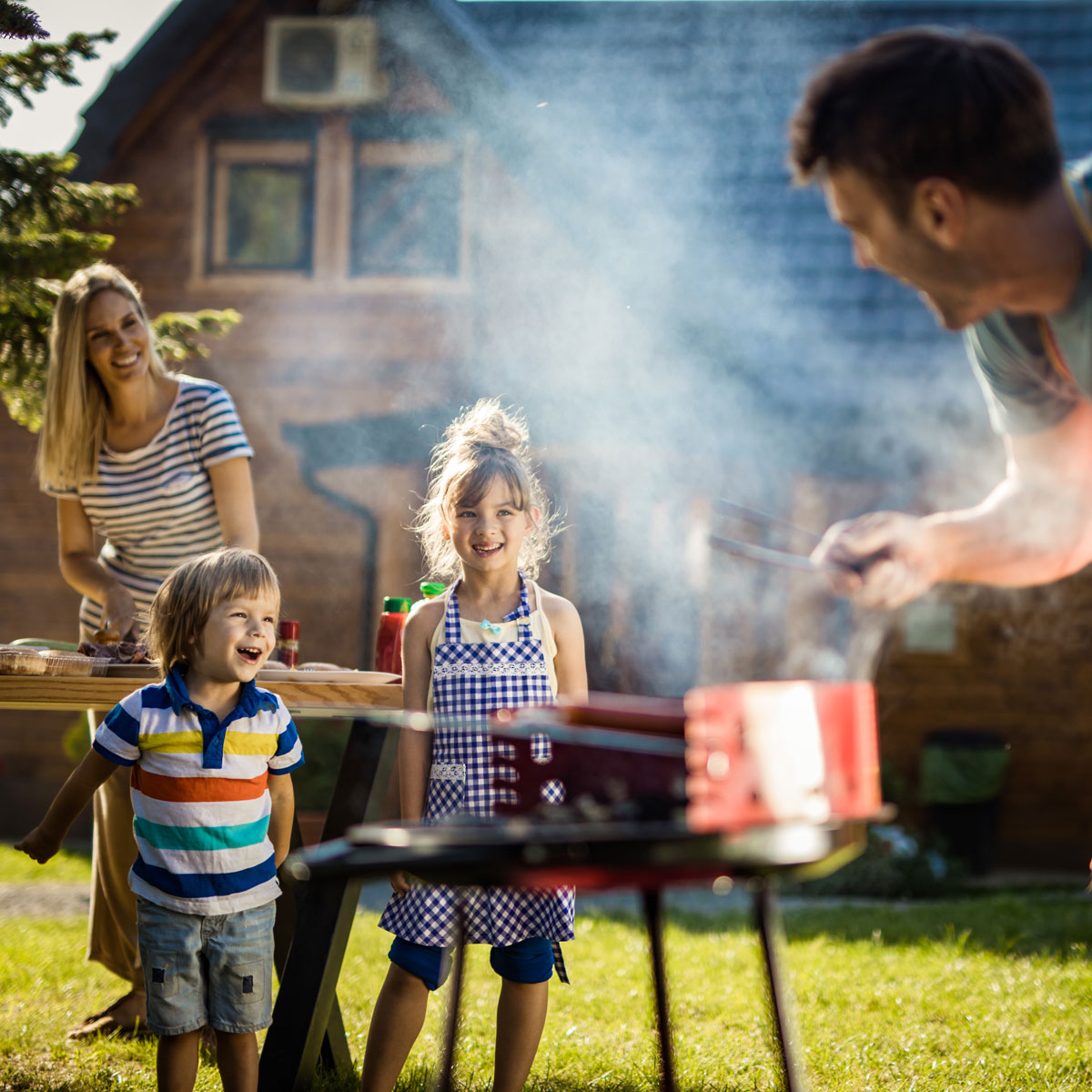 Family grilling outside at picnic table